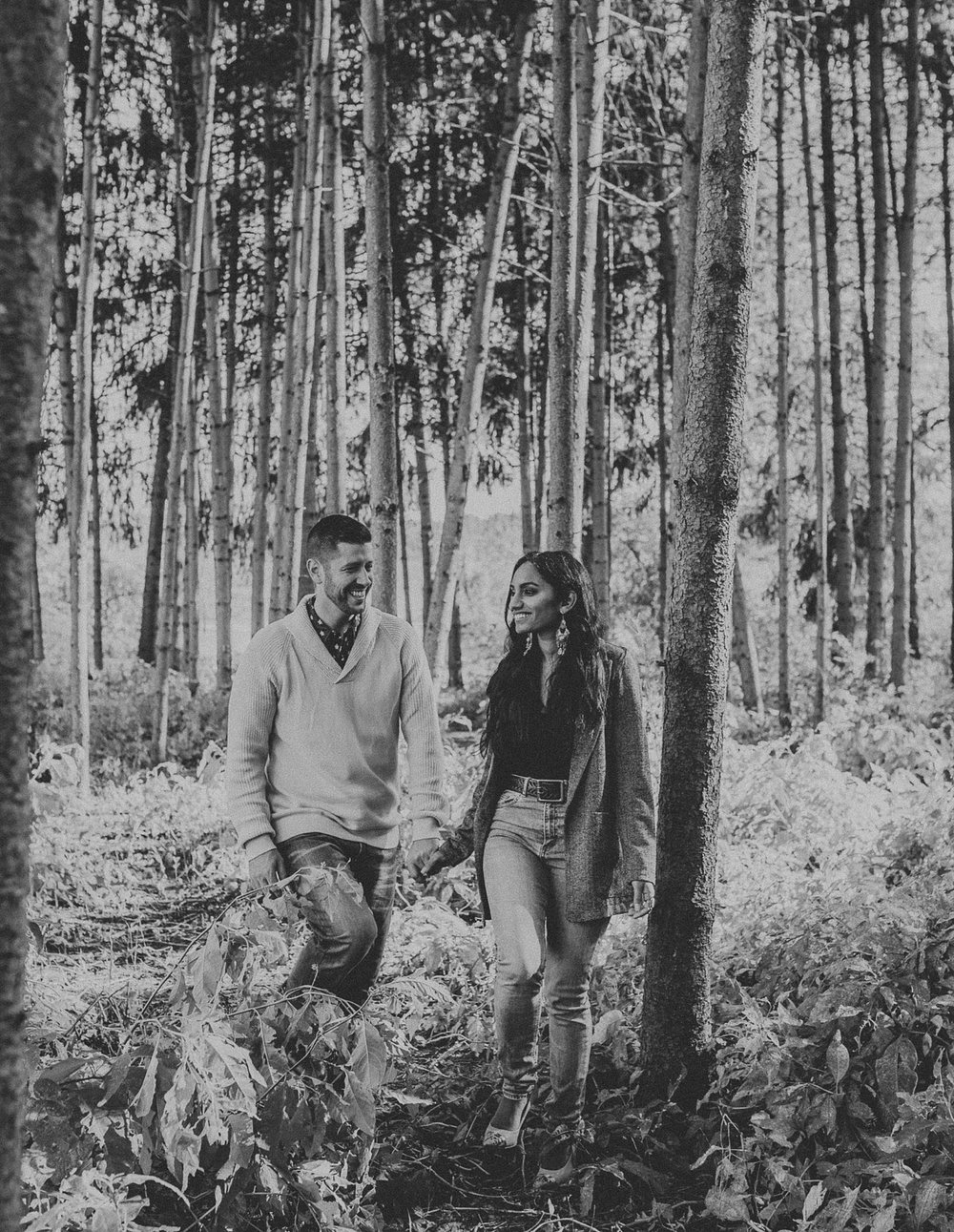Couple walking through woods together while holding hands during photo shoot at Overlook Community Park in Lancaster, PA