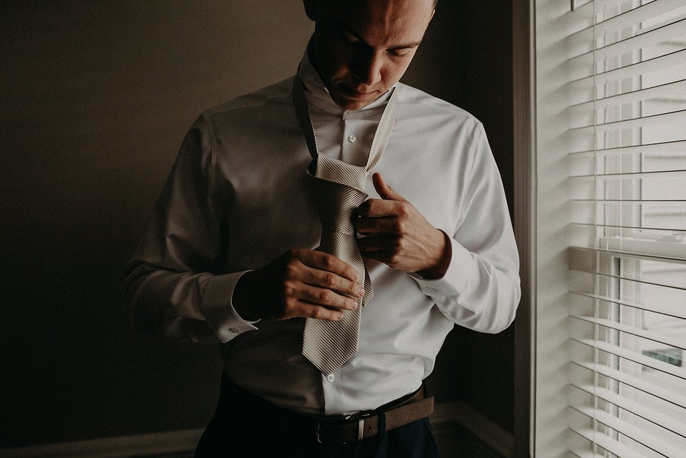 Groom tying his own tie while getting ready on wedding day