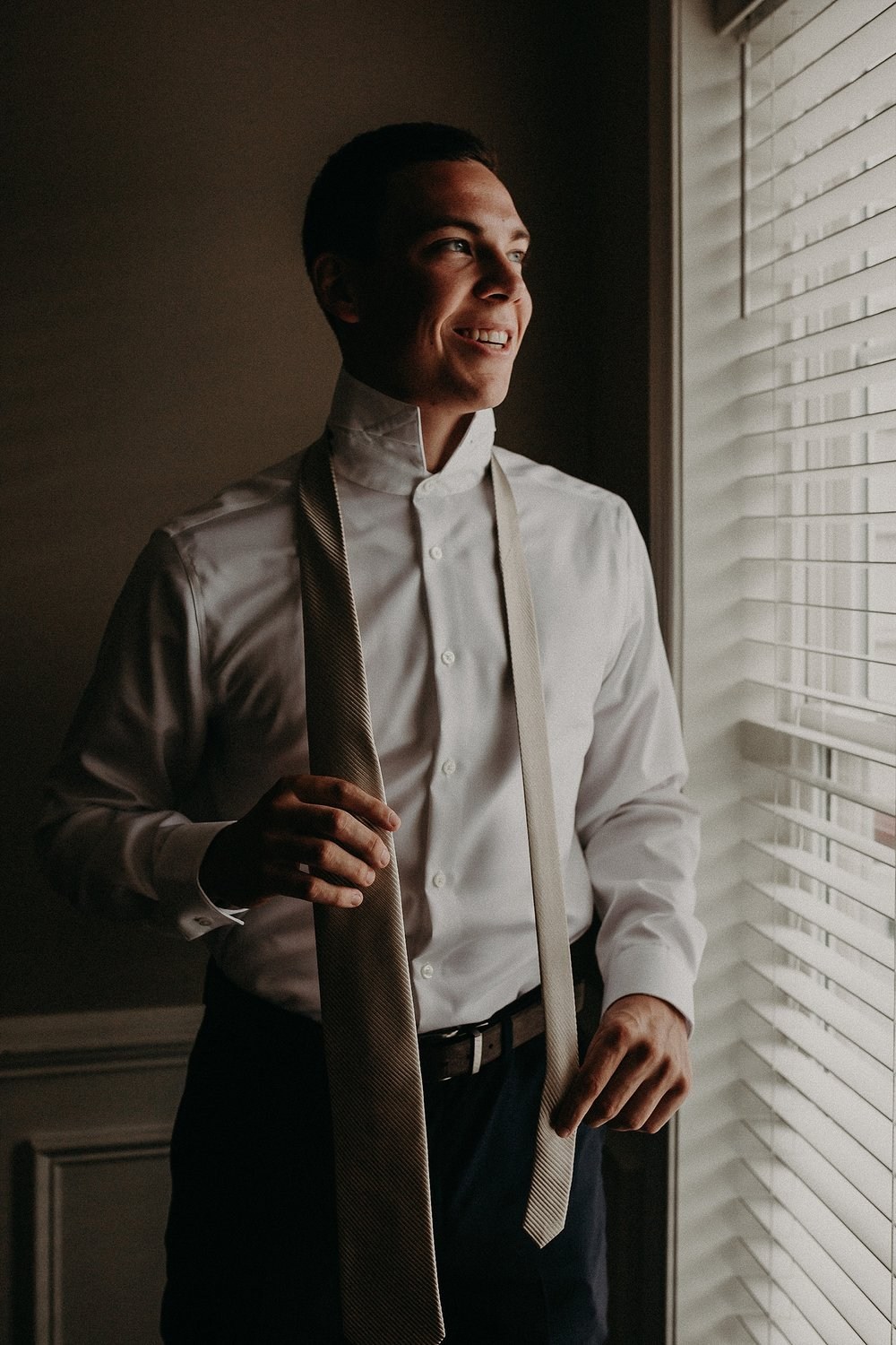 Smiling groom tying tie on wedding day