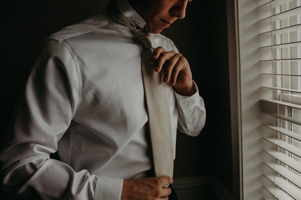 Groom putting his final touches on himself while getting ready for wedding day