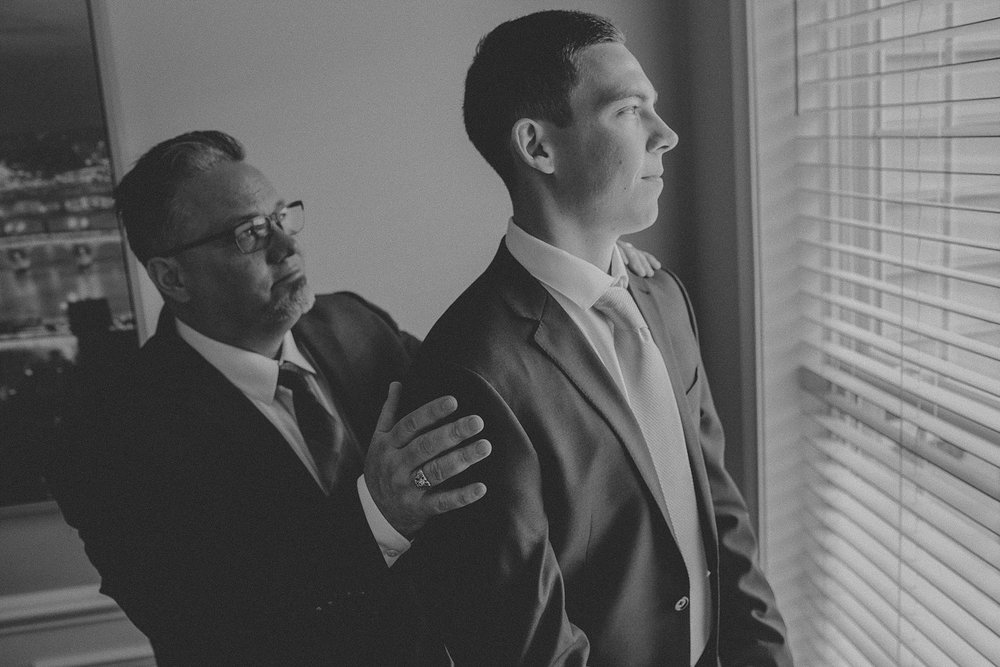 Father helping Groom put on his suit jacket while getting ready on Wedding Day