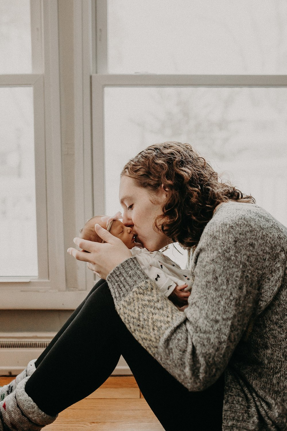 New mother kissing tiny newborn on cheek during in home newborn lifestyle photoshoot in Lancaster, PA
