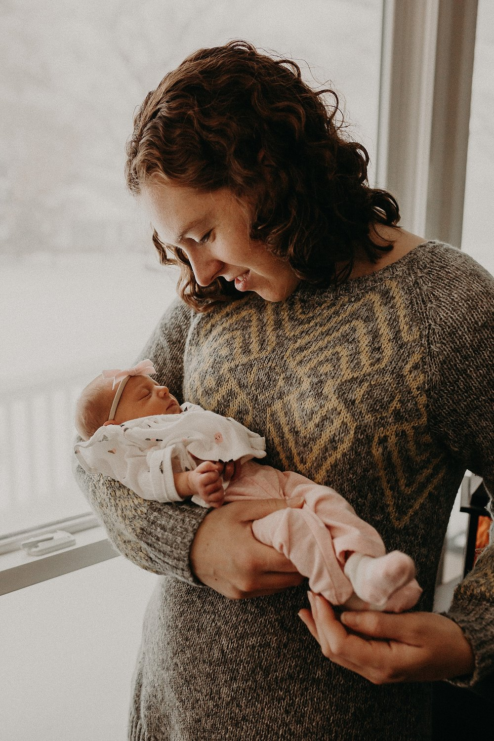 Mother cuddling sweet newborn during in home newborn lifestyle photoshoot in Lancaster, PA