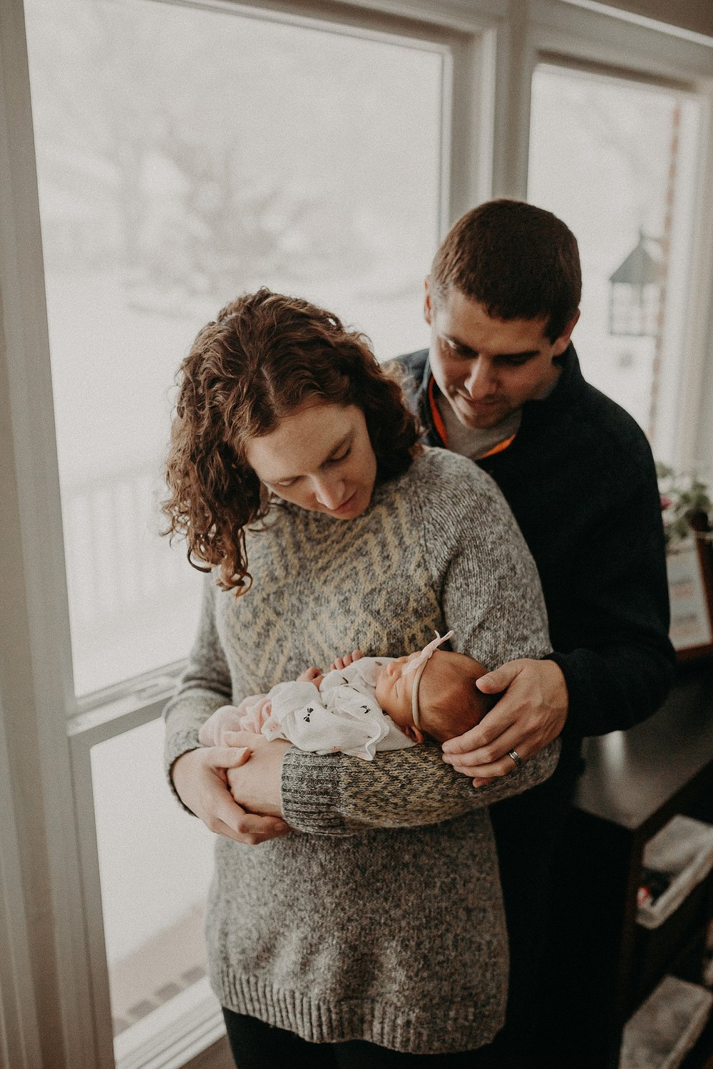 Family of three cuddling together during in home newborn lifestyle photo session in Lancaster, PA