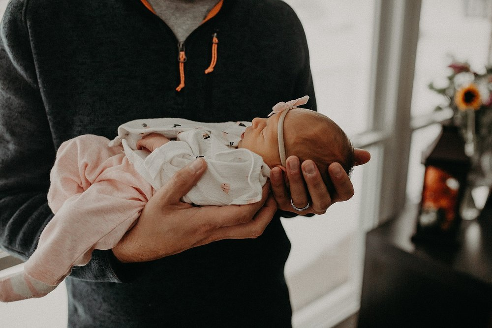 Father holding tiny newborn gently during in home newborn lifestyle photoshoot in Lancaster, PA