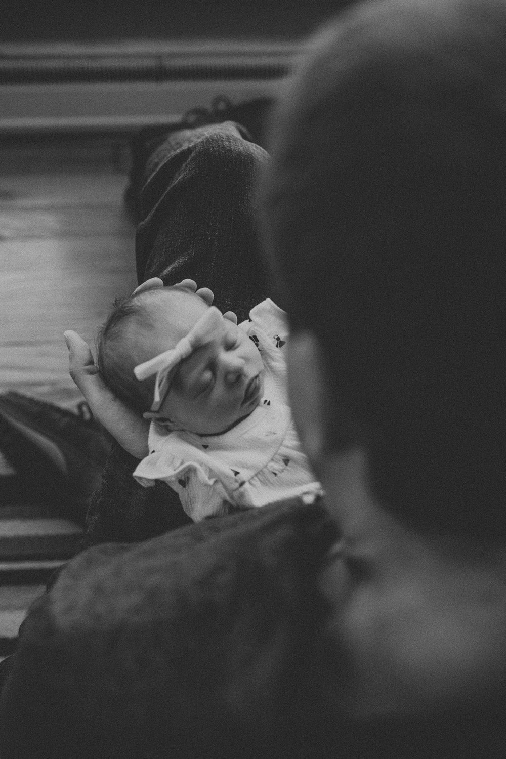 Tiny baby newborn being held by father during in home newborn lifestyle photo session in Lancaster, PA