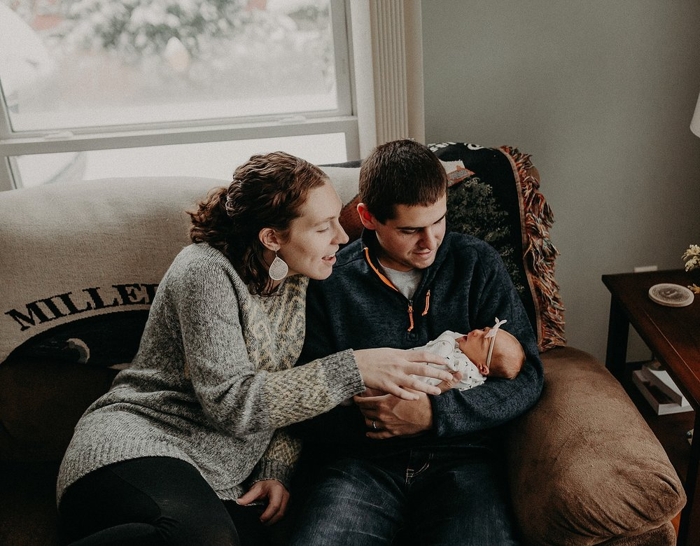 Family of three sitting together on couch during a snow storm during in home newborn lifestyle photo session in Lancaster, PA