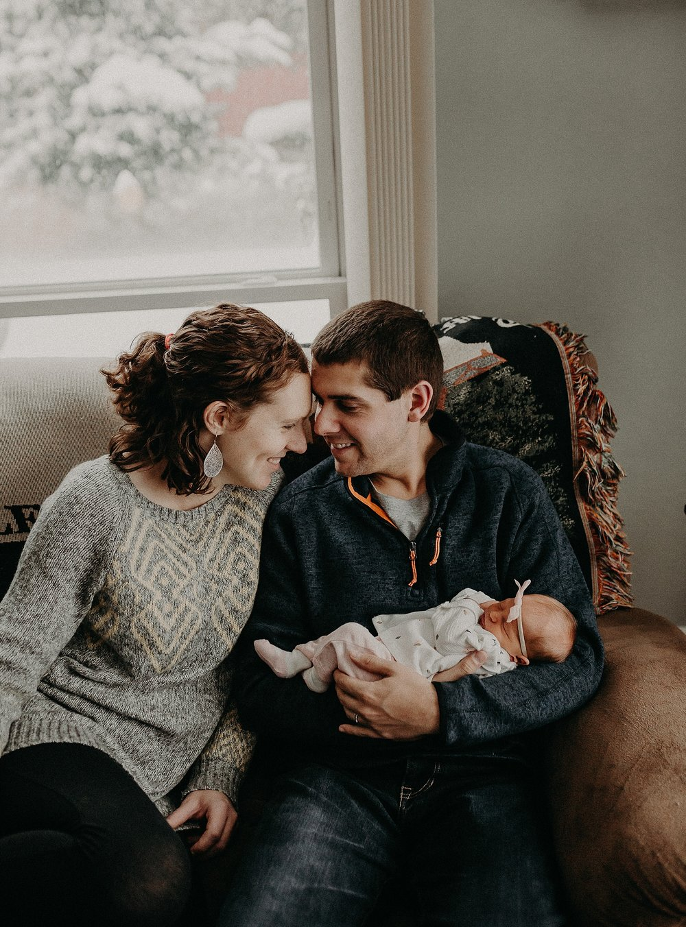 Mom and Dad having a loving moment during in home newborn lifestyle photoshoot in Lancaster, PA