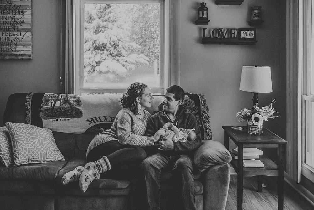 Family of three keeping warm and cozy during a raging snow storm during in home lifestyle photo session in Lancaster, PA