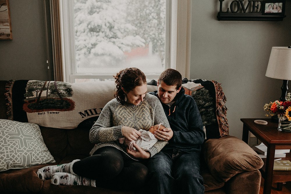 Father, Mother, and newborn daughter having sweet cuddles during in home newborn lifestyle photoshoot in Lancaster, PA