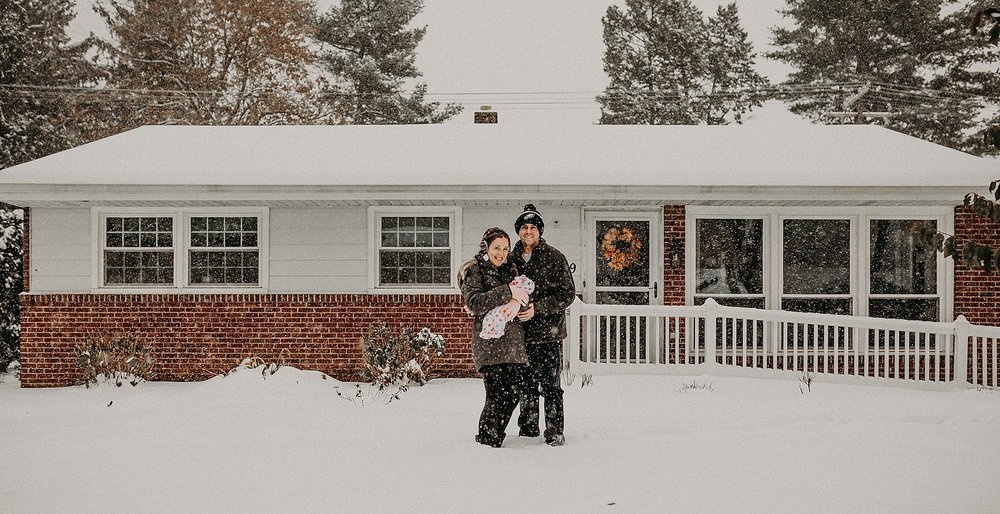 Family photos during fluffy snowstorm during in home newborn lifestyle photoshoot in Lancaster, PA