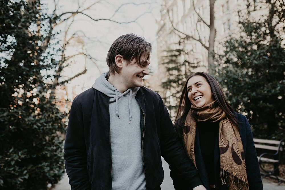 Couple in love having engagement photos taken in Washington Square Park in New York City, New York