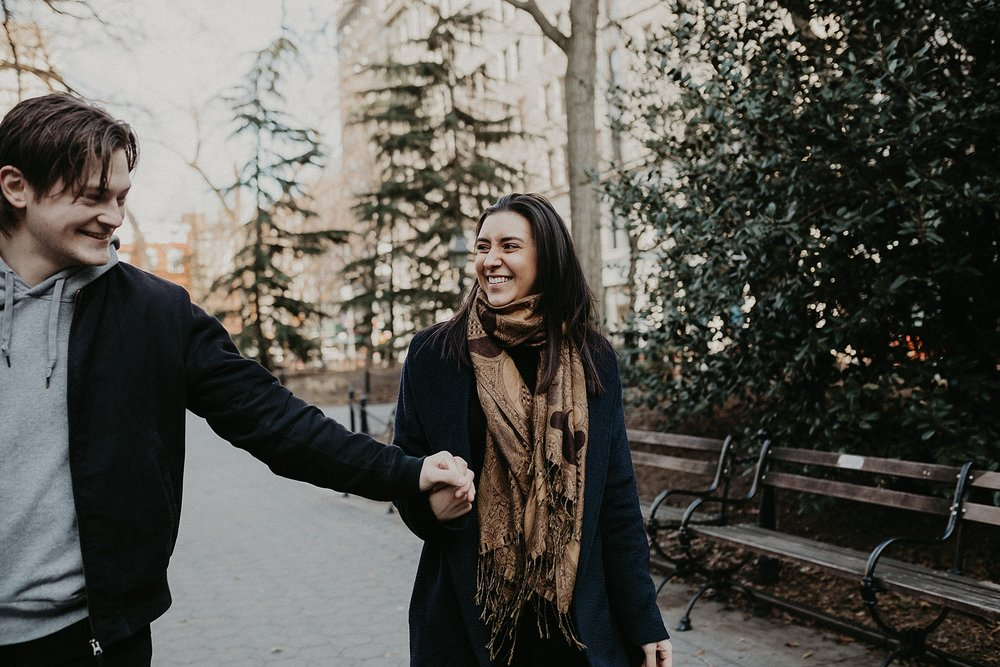 Couple strolling through Washington Square Park during engagement session in New York City, New York