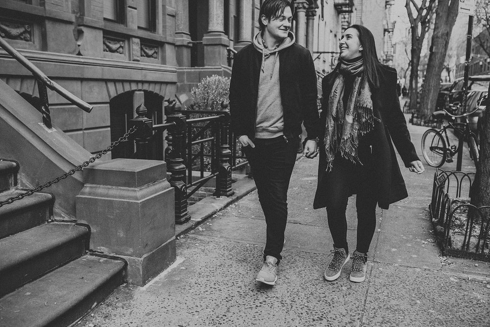 Couple walking and holding hands on the streets of New York City during engagement session