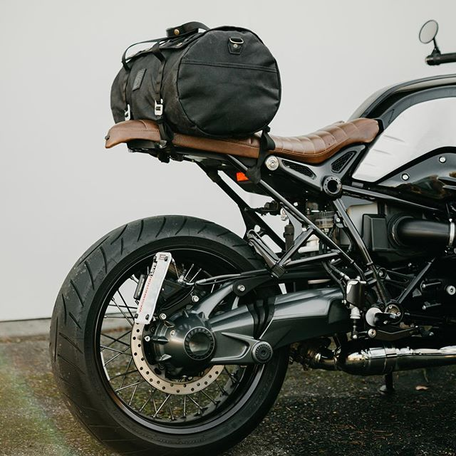 LAST CHANCE! It's Cyber Monday which means our holiday weekend sale is coming to a close tonight at midnight. No discount code necessary, sale prices are already applied on our site.  Pictured here is our new lightweight duffle bag in all black on @seattlebull's BMW R nine T. Swipe through the photos to get a better idea for how our simple webbing & G-hook mounting straps wrap around the subframe and attach to the tubular molle webbing on the duffle.