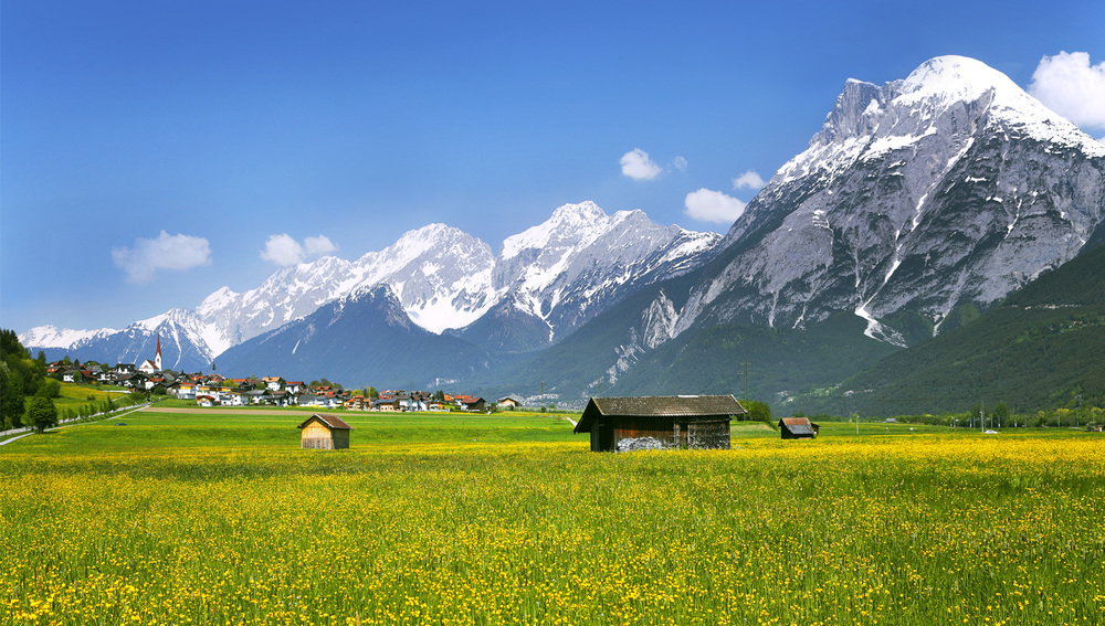 Fields of flowers bloom during the Austrian summer, carpeting the Inn Valley. Here, the Hohe Munde mountain range towers above a picturesque settlement. Photograph from Photolibrary.