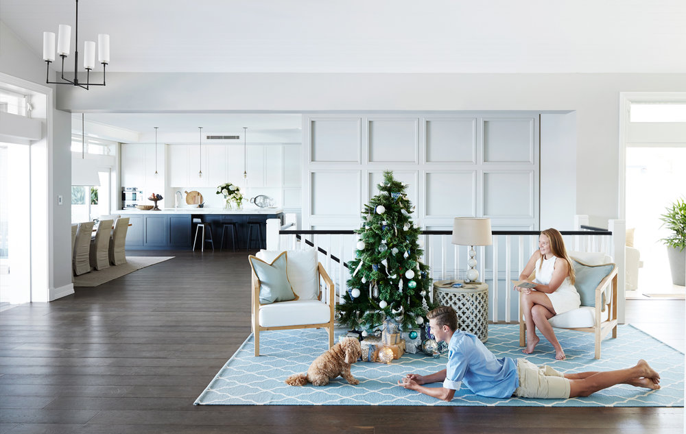The stairs and one wall are all that remain of the original home. Furniture placement and rugs demarcate zones in this open-plan space, with the selective use of detailed panelling creating a sense of intimacy. Teenagers Declan and Taylor, with cavoodle Bolli, enjoy the build up to Christmas Day.