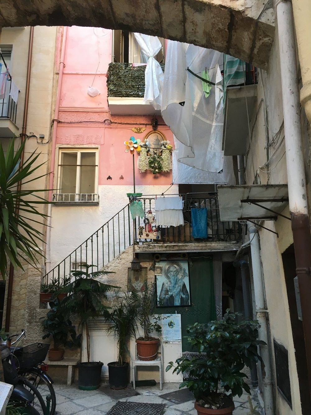 Neighboring Courtyard with Three Posters of Different Saints, and Laundry