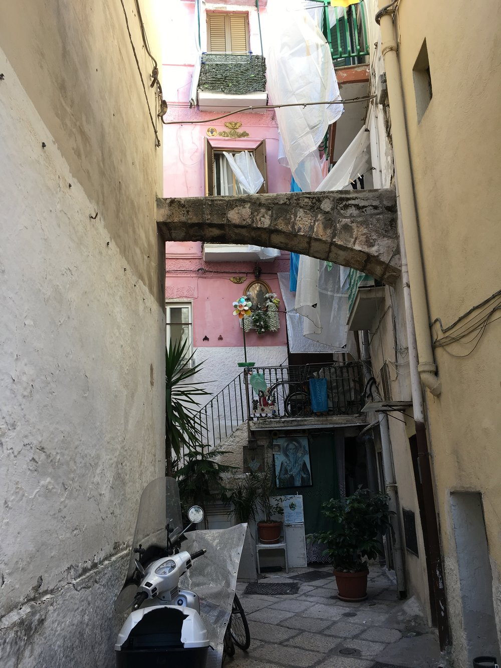 A neighboring courtyard with three posters of different saints, and laundry