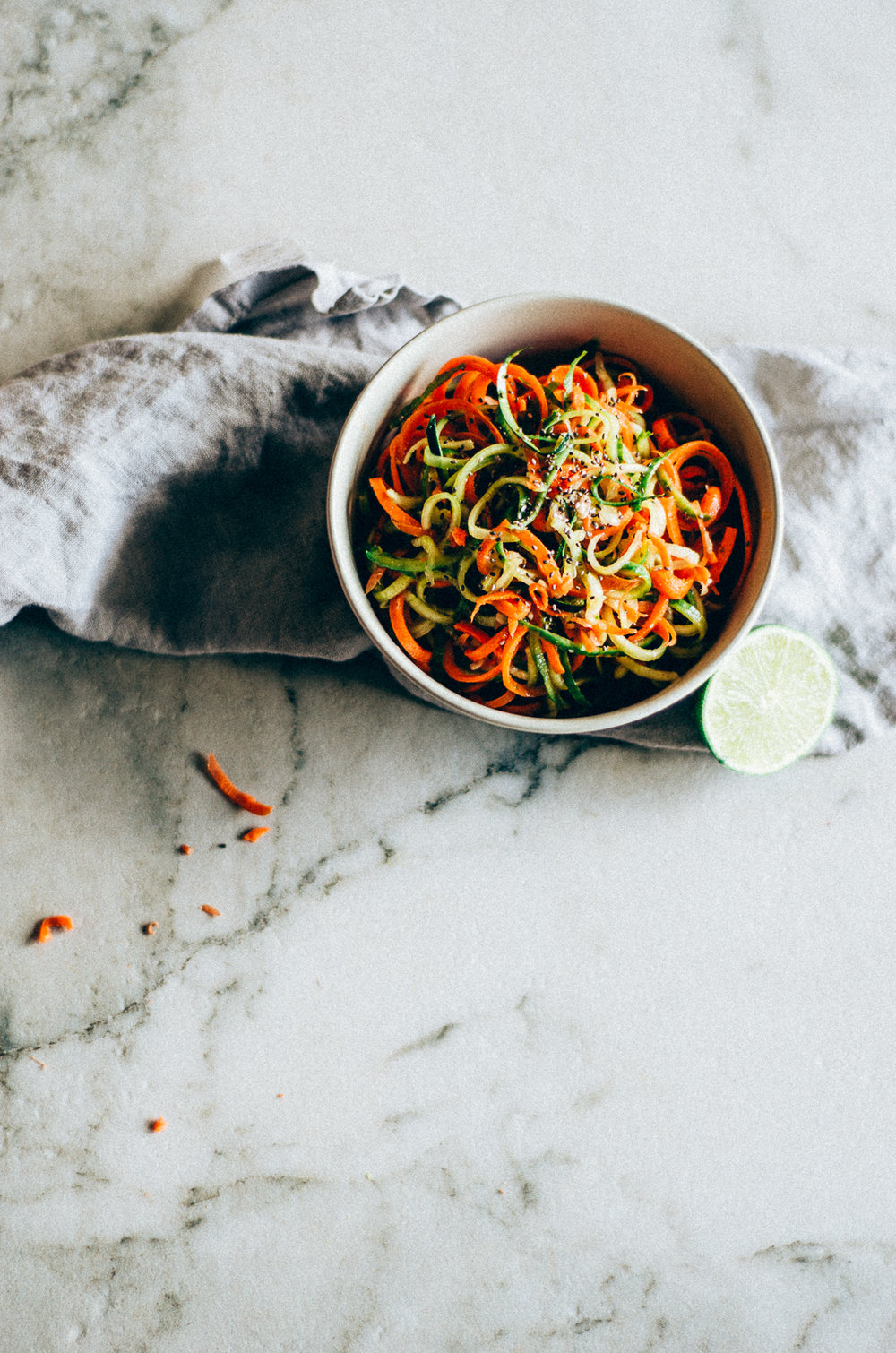 Spiralized Asian Salad Recipe with carrot & cucumber featuring a spicy lime sauce. Reminds me of food I ate in singapore. thenomadicwife.com