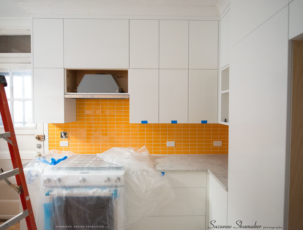 At today's site visit we selected a wall paint color to go with these custom cabinets and orange (sunset) back splash !!