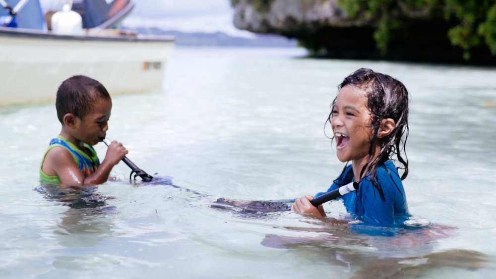 Children playing in the ocean, Palau.