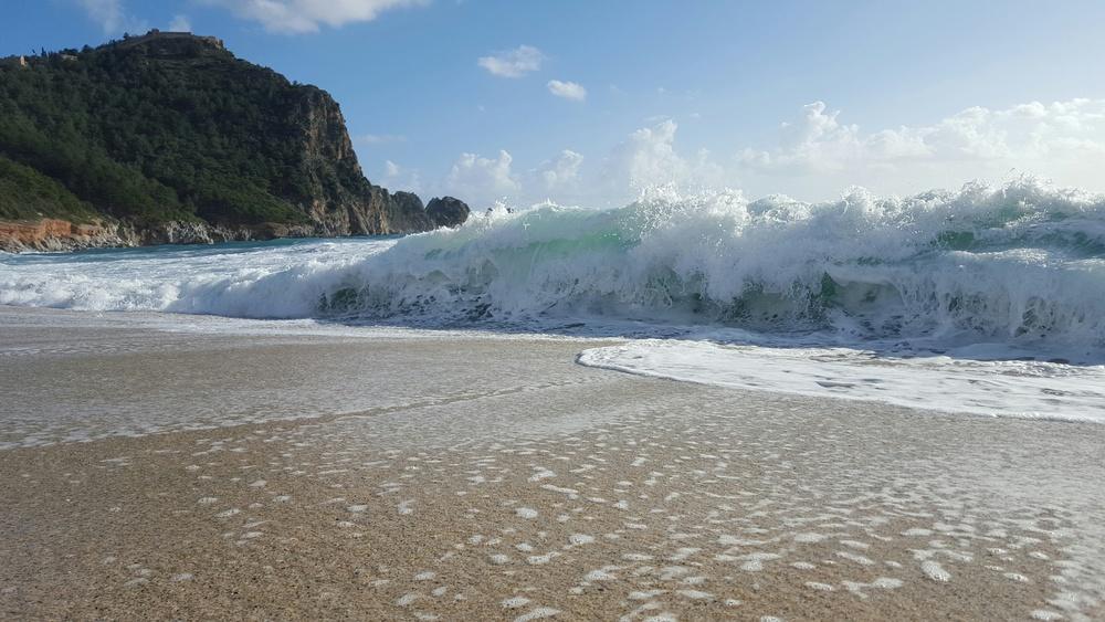 A wave breaks on the beach at Alanya, Turkey
