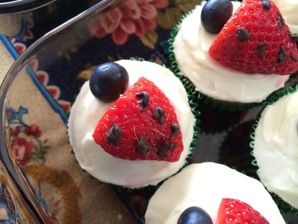 Easy to make strawberry ladybug cupcake garnish with blueberries and chocolate dollops.