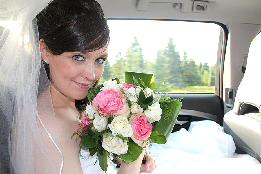 bride in car with pink roses