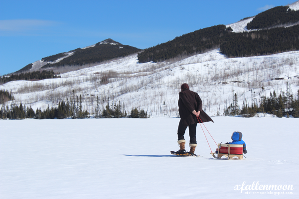 mom pulling baby on sled