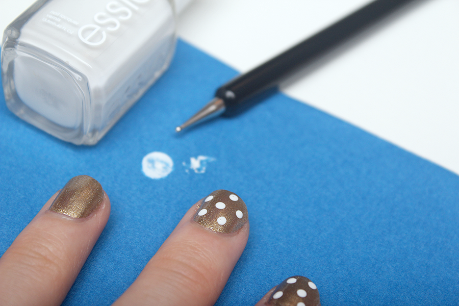 white dots on gold nail
