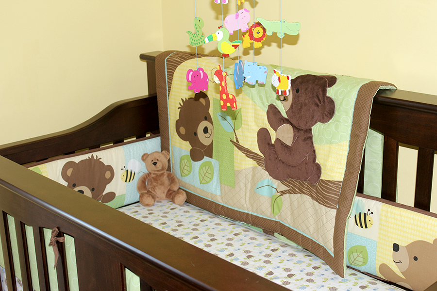 brown crib with green bedding