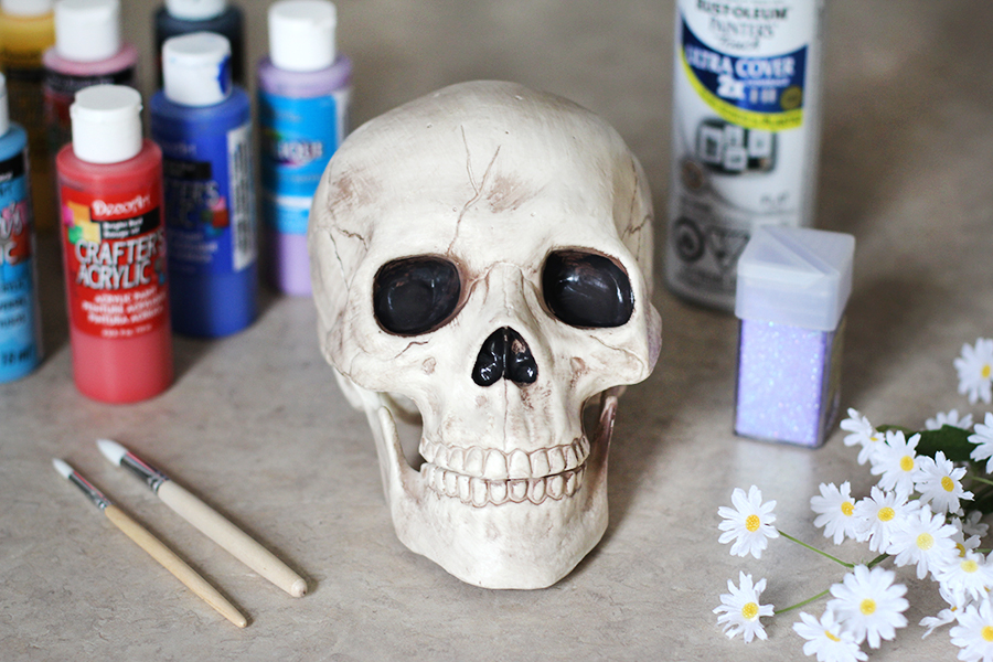 The materials to make a Halloween sugar skull candy bowl; skull, paint, paint brushes, sparkles, flowers.