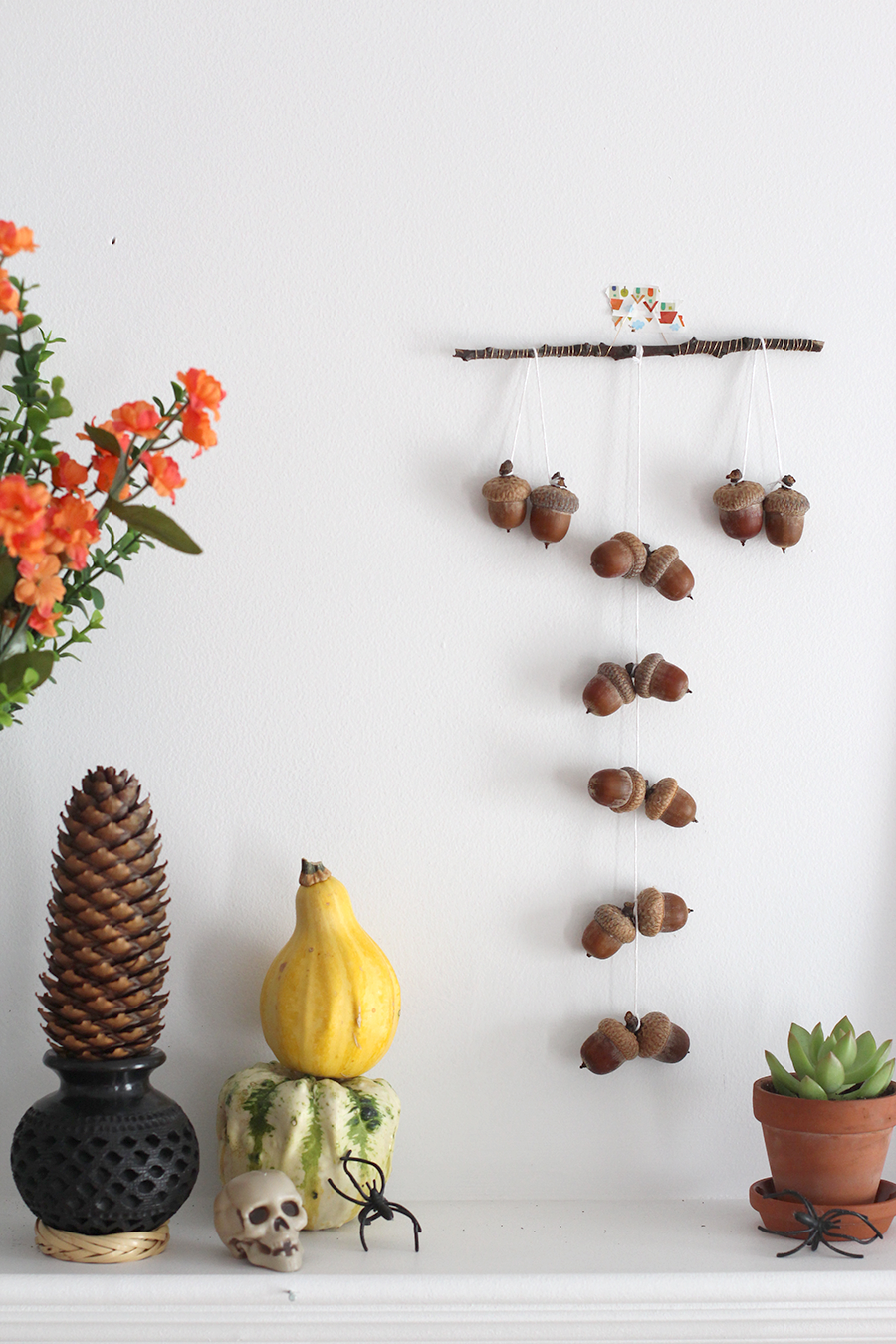 Learn to make your own fall acorn mobile to decorate your lovely living room fire mantle.