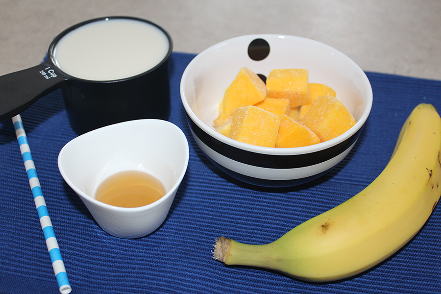 The ingredients for a super quick milkshake; banana, mango, milk and maple syrup.