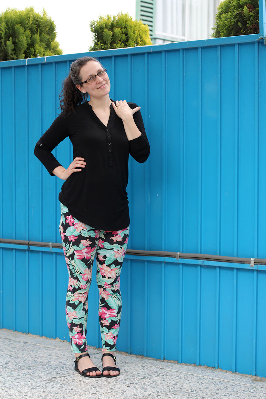 Super fun and comfortable outfit for a busy mom. Flat sandals, floral leggings, and a loose black shirt.