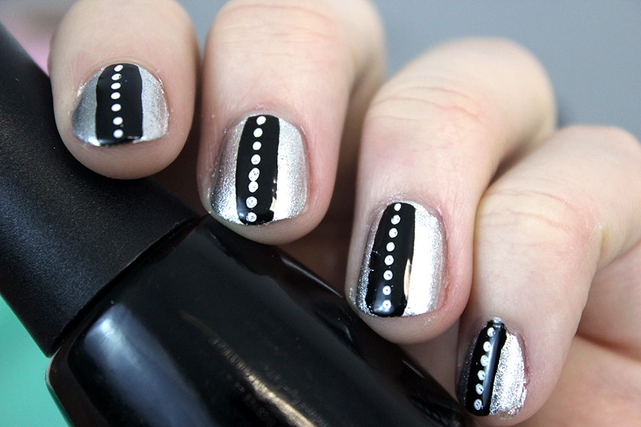 Black and silver nail art; silver base, black line, white dots.