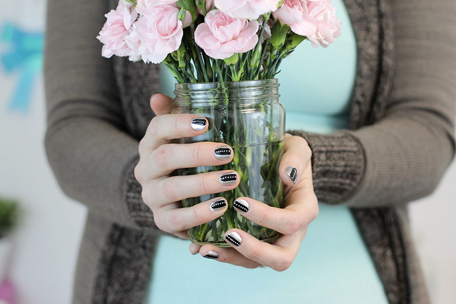 Showing off my pretty black on silver nail art with white dots while holding a flower pot.