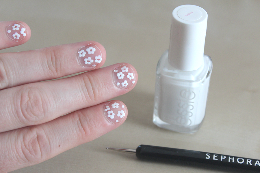 Make little clusters of 5 white dots on bare nails.