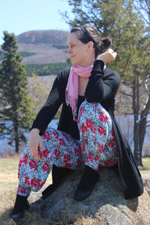 sitting on a rock wearing flower pants.jpg