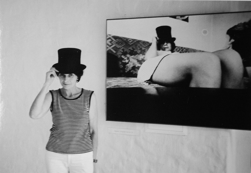 Zenta Dzividzinska        (1944-2011) in her solo exhibition in gallery  Ciris,  Riga, 1999, posing in front of her  Self-portrait,  1968 (gelatin silver print, printed in 1999, 90 x 130 cm).