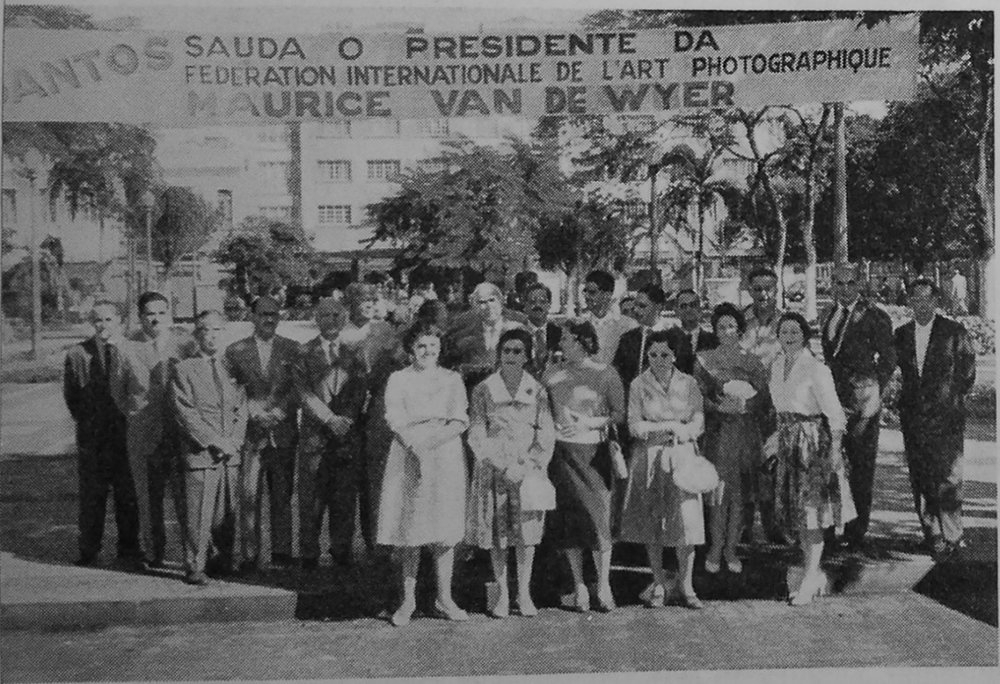 """Reception of the President of FIAP [Maurice Van de Wyer] in Santos, Brazil, by the authorities and the [photo] club in 1960. The transparencies were mounted in front of the City Hall.""  Camera,  no. 1 (1961). 48."