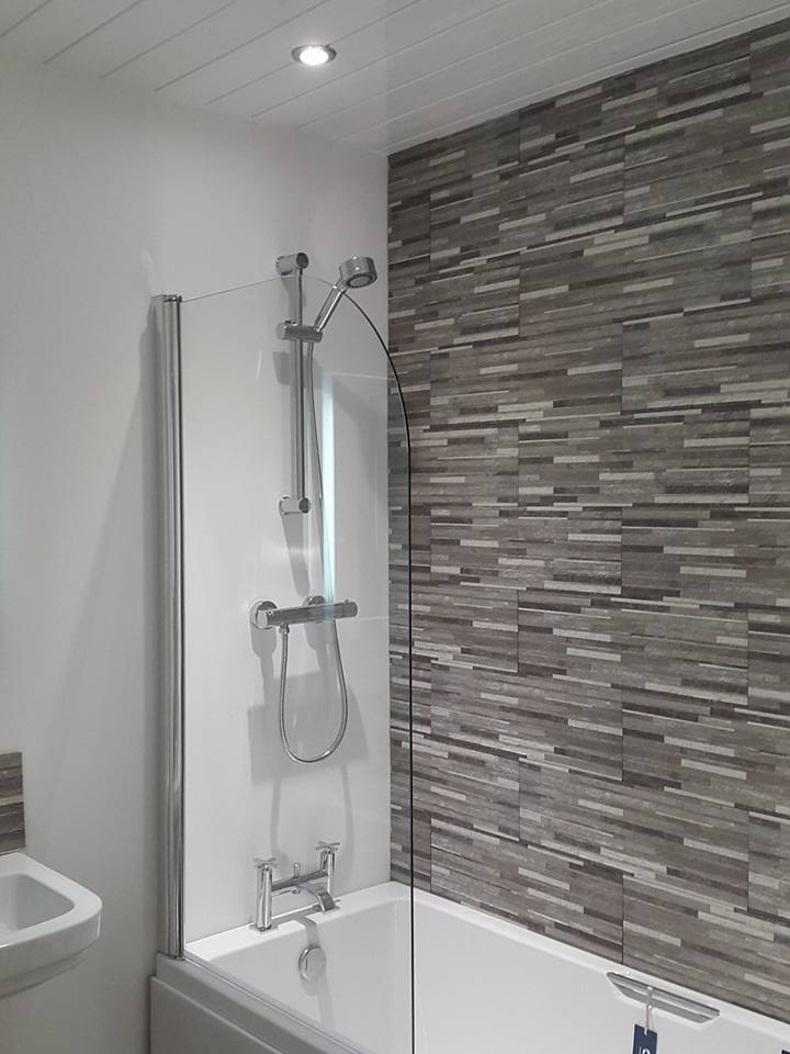 Bath with integral shower and tiling on display in our showroom