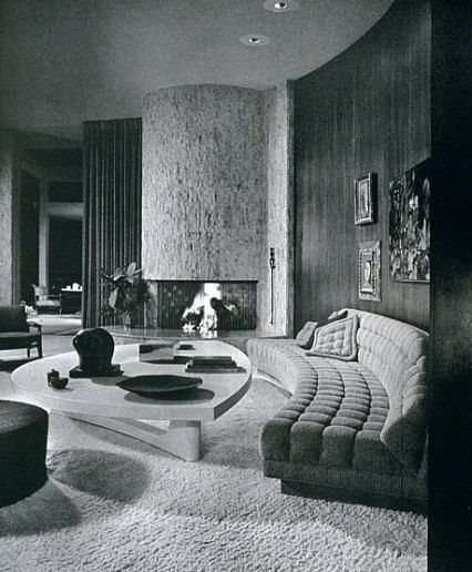 The living room of Mr. and Mrs. Eugene V. Klein's Trousdale Estates, Beverly Hills, residence. The room features a walnut paneled wall, custom tufted curved sofa, coffee table of picked cork and a large travertine fireplace. Interior design by Arthur Elro