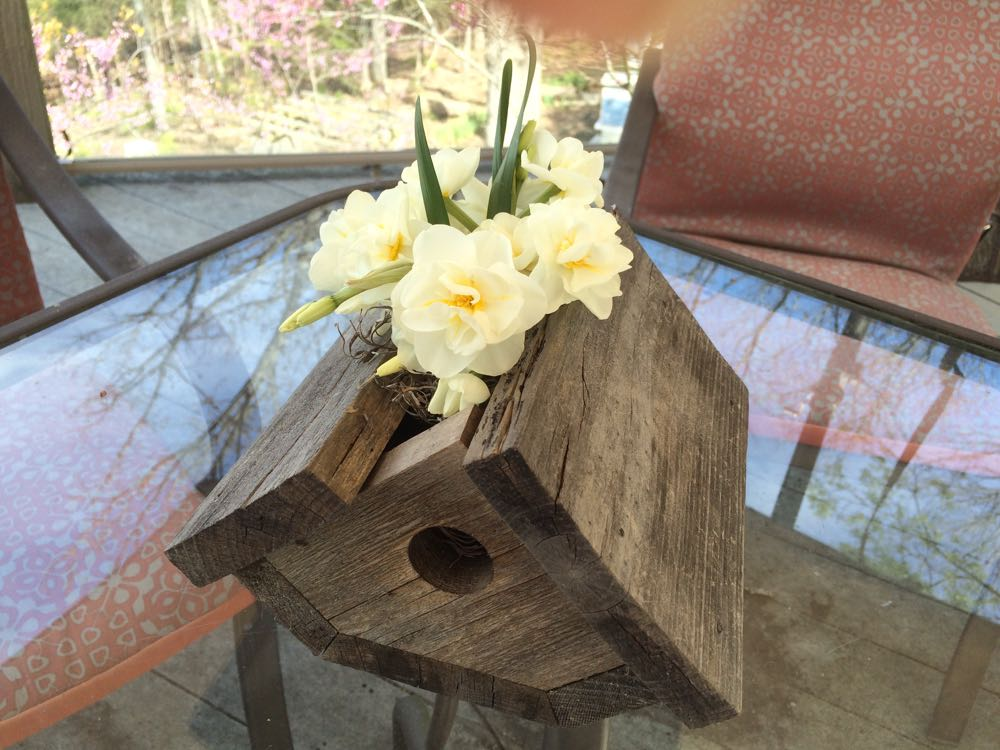 Broken birdhouse repurposed into a table top flower vase easily works outside on a deck.