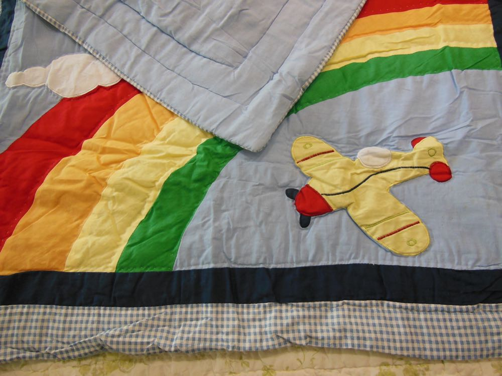 High Flying Baby Crib Quilt has a navy blue strip for custom embroidery to personalize.