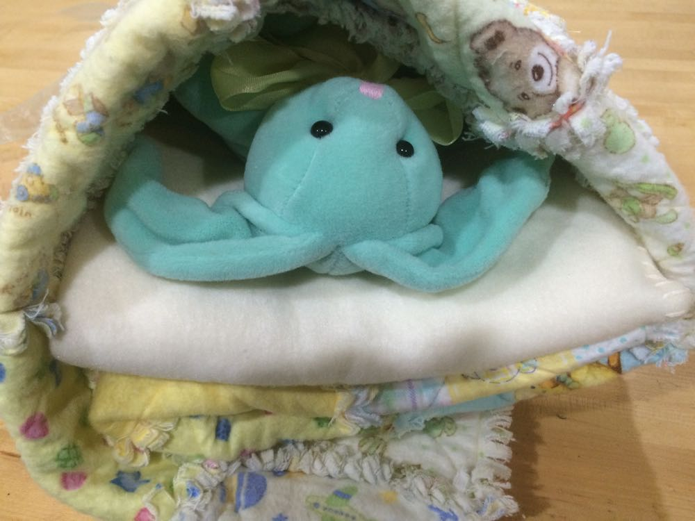 Rabbit toy wrapped in Bluebird Gardens yellow rag baby quilt.