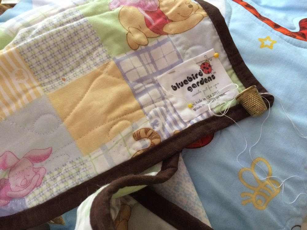 I add care tags to our custom baby crib quilts before packing for shipping.