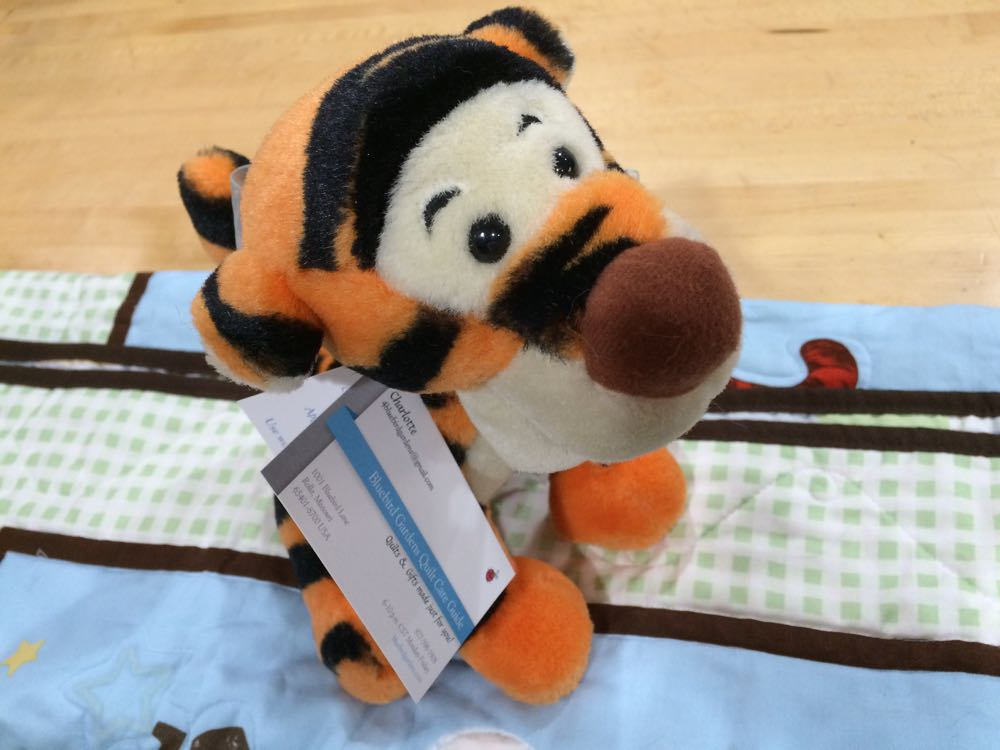 Tiger toy delivers the quilt care guide for the custom Pooh Bear baby crib quilt.