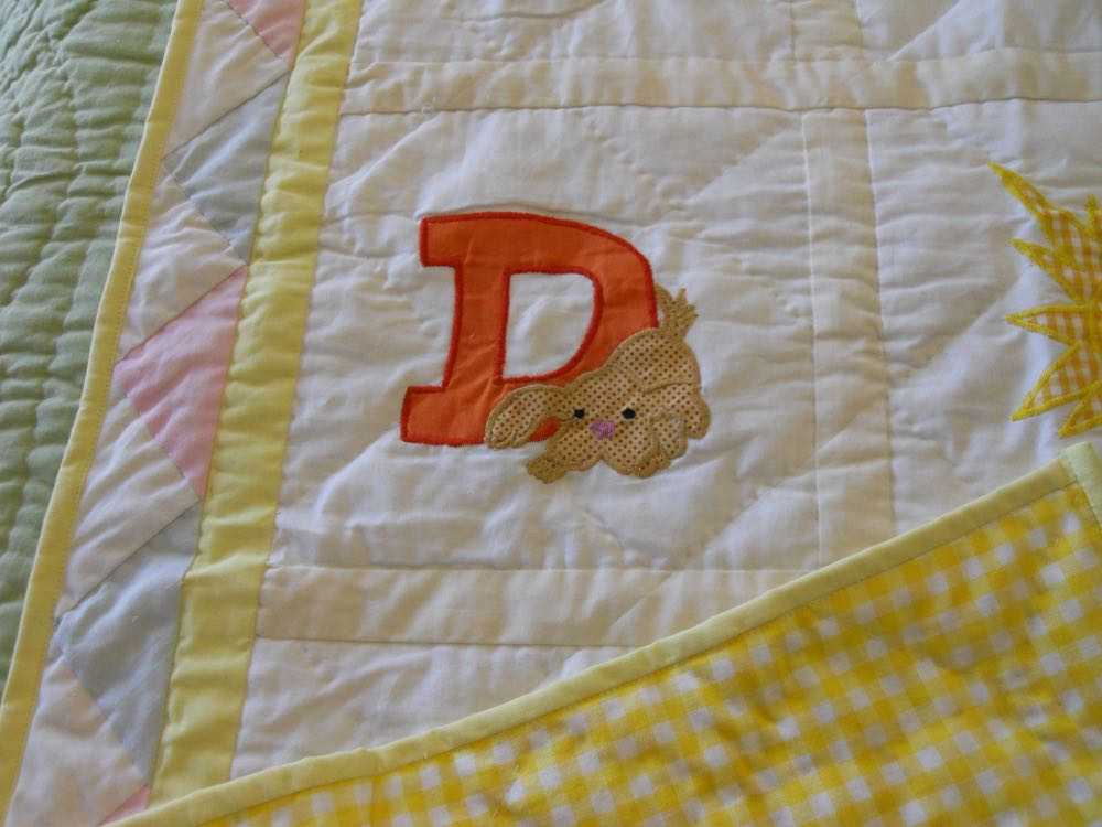 ABC in Clouds Baby Crib Quilt has a bright yellow and white checked backing.